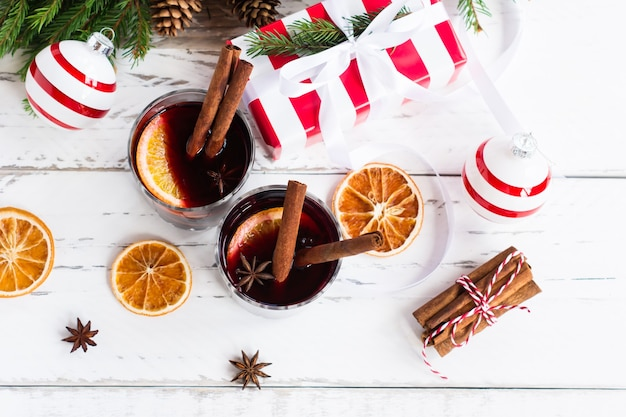 Два бокала горячего глинтвейна украсили пряностями и сушеными апельсинами. праздничная открытка на рождественские праздники, вид сверху