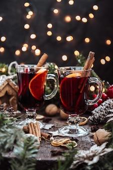 Два бокала глинтвейна в новогодней обстановке, горячее вино. красивое новогоднее украшение