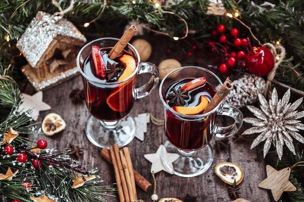 Два бокала глинтвейна в новогодней обстановке, горячее вино. красивое рождество