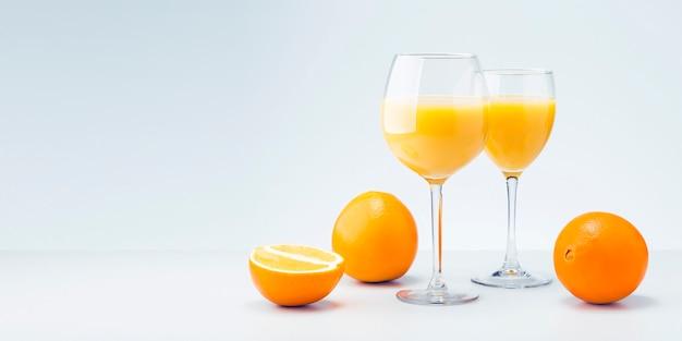 Два стакана апельсинового сока и фруктов с копией пространства.