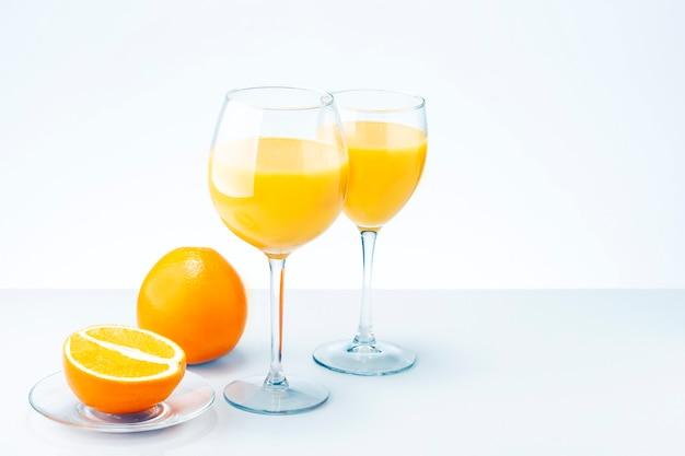 오렌지 주스 칵테일 및 복사 공간 밝은 회색 표면에 과일 두 잔.
