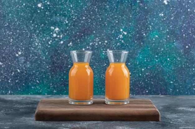 Два стакана апельсинового сока на деревянной доске.