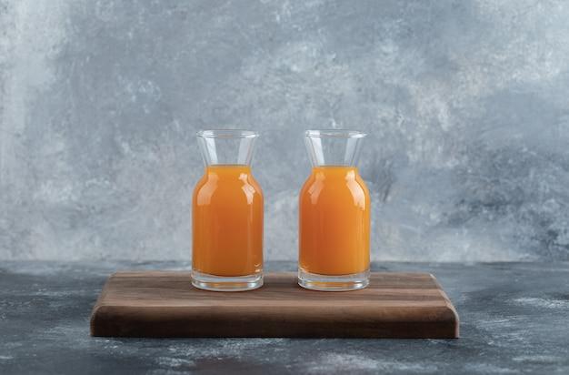 나무 보드에 오렌지 주스 두 잔입니다.