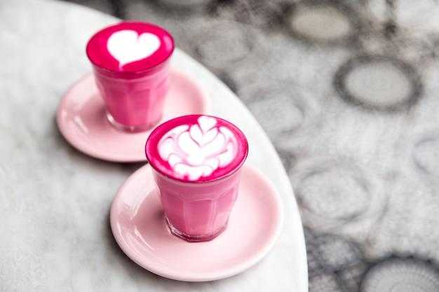 대리석 테이블 배경에 아름다운 라떼 아트가 있는 분홍색 비트 뿌리 라떼 두 잔. 트렌디한 건강 음료.