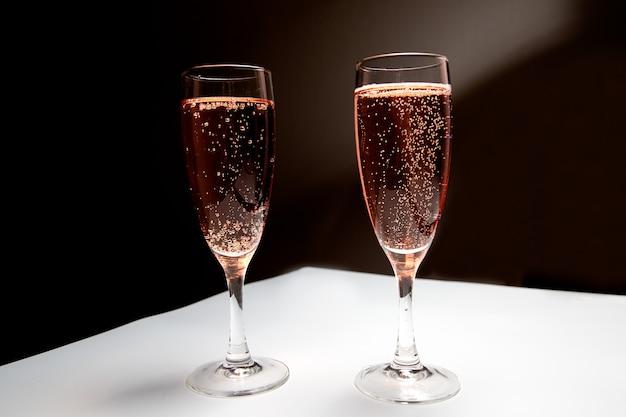 흑백 배경에 분홍색 샴페인 두 잔