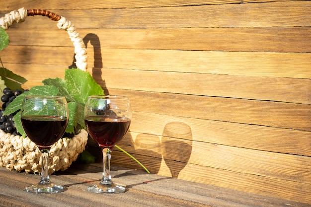 Два бокала красного вина и корзина с виноградом на деревянном фоне