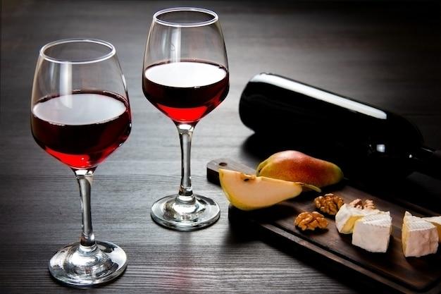 木製のまな板に赤ワイン2杯とワイン、チーズ、梨、クルミのボトル