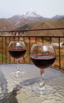 雪をかぶった山を背景にガラスのテーブルに赤ワイン2杯