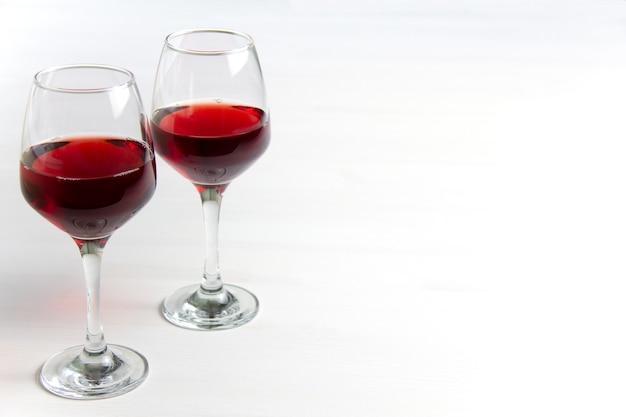 Два бокала красного вина на белом