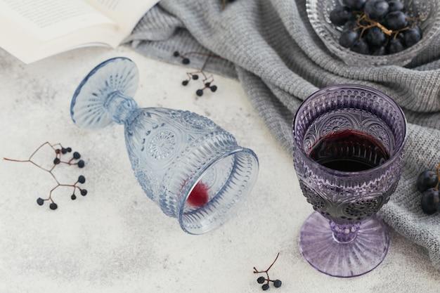 Два бокала красного вина с книгой, темный виноград и сухие ягоды на свету