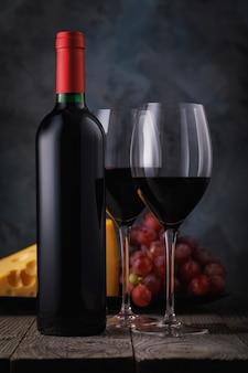 木製のテーブルにチーズとブドウと赤ワイン2杯