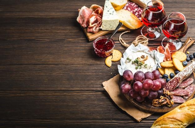 Два бокала красного вина, деревянная доска, холодное мясо, сыр, фрукты, соус. деревянный фон