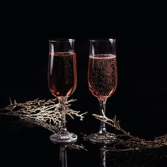 Два бокала розового шампанского и рождественские или новогодние украшения на черном