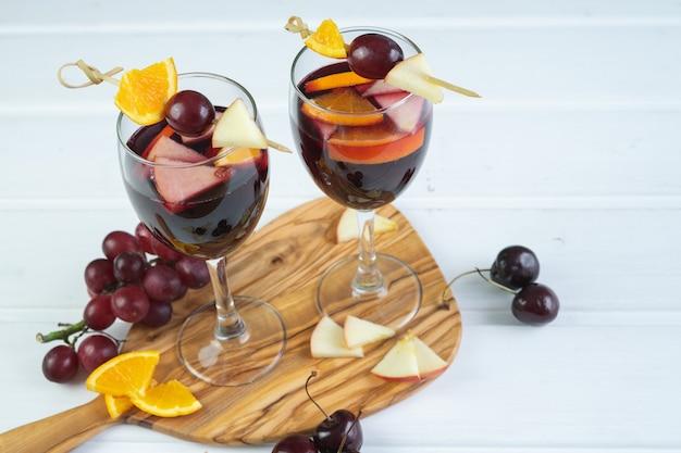 白い木製のベースにサングリアを2杯。フルーツの装飾が施された伝統的なスペインの飲み物。スペースをコピーします。