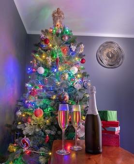 Два бокала игристого шампанского в новогоднюю ночь с часами, показывающими две минуты до полуночи. рождественские украшения .