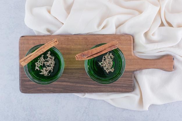 木の板にシナモンが入ったタラゴンジュース2杯。高品質の写真