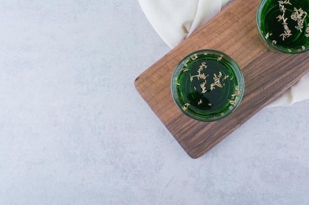 木の板にハーブとタラゴンジュースの2杯。高品質の写真