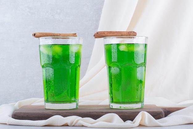 木の板に氷とタラゴンジュース2杯。高品質の写真