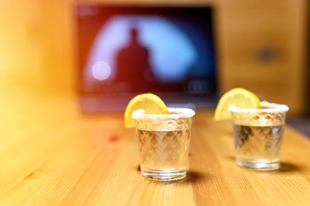 映画を見ながらノートパソコンの背景にテキーラを2杯。自宅で楽しい夜。