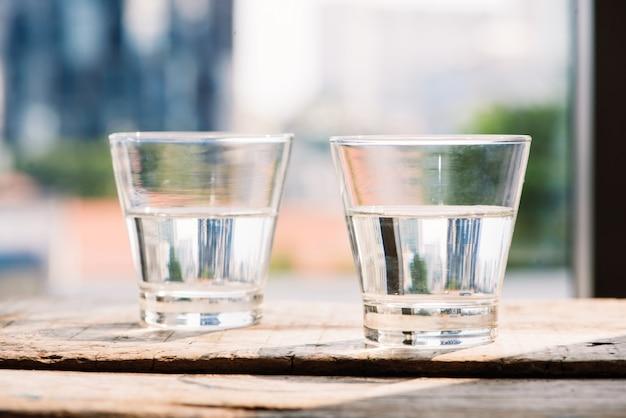 木製の背景の上のテーブルに水2杯