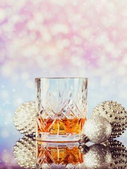 가벼운 bokeh 배경에 크리스마스 장식과 함께 위스키 또는 버번 두 잔. 새해, 크리스마스 및 겨울 휴가 위스키 분위기 개념