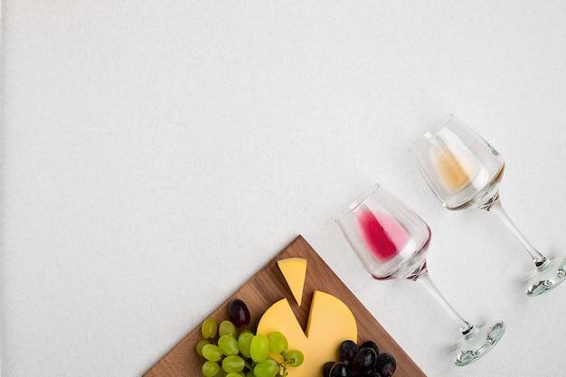 Два стакана белого и красного вина, сыра и винограда, вид сверху