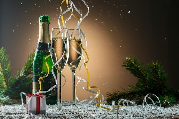 Два бокала белого шампанского, открытая бутылка и елочные игрушки, еловые ветки, серебряная подарочная коробка, каскадные ленты и снежинки.