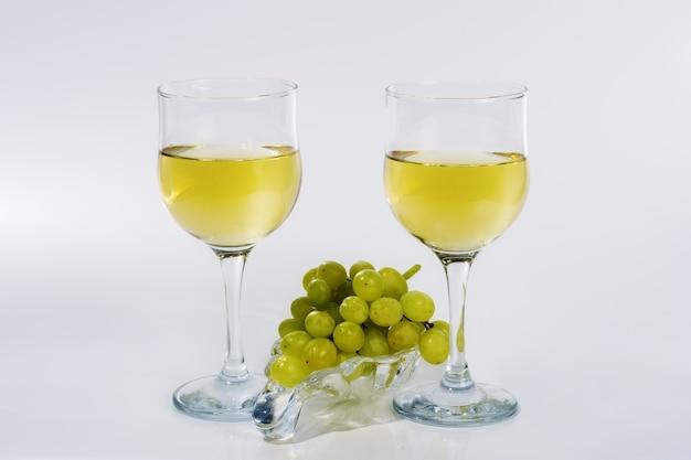 白ワイン2杯とガラス板上の緑のブドウの束