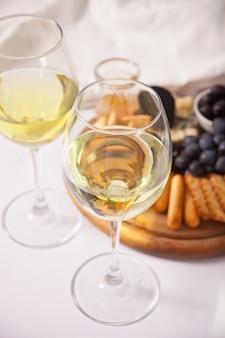 Два бокала белого вина и тарелка с ассорти из сыра, фруктов и других закусок для вечеринки