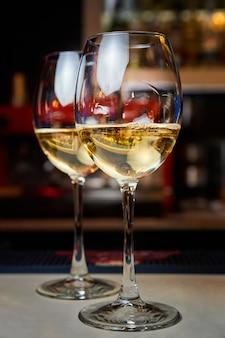 Два бокала белого вина на стойке