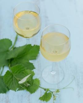 Два бокала белого вина с листьями винограда на голубом