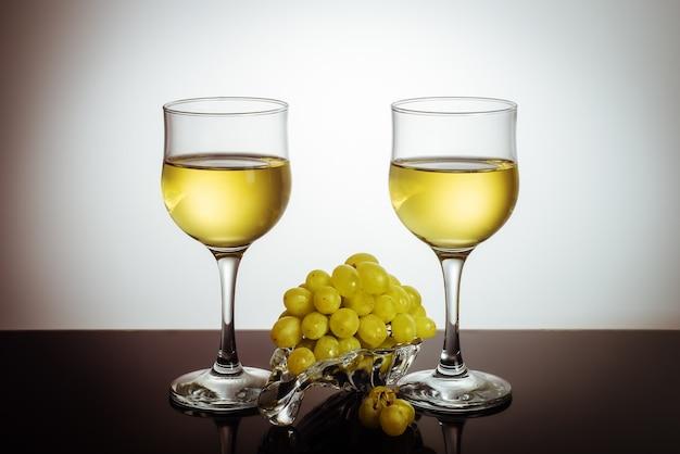 ガラス板に2杯のワインとブドウの房