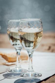 ビーチでのピクニックにグラス2杯のワインとパン