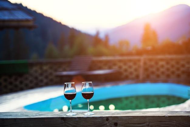 山の風景の背景に日没の劇的な空でワイン2杯