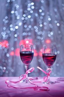Два бокала вина в сочетании с концепцией розовой ленты на день святого валентина