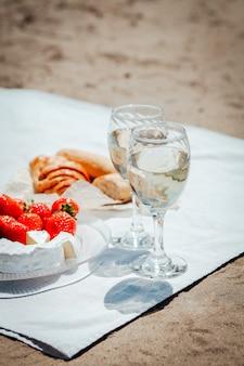 ビーチでのピクニックにワイン、イチゴ、チーズ、ブルーベリー、パンを2杯