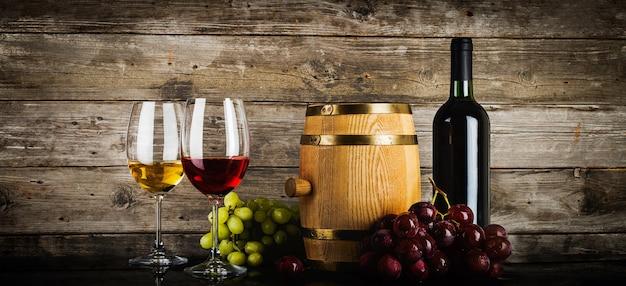Два бокала вина со свежим виноградом фреш, бутылка и бочка перед старыми деревянными досками в стиле гранж