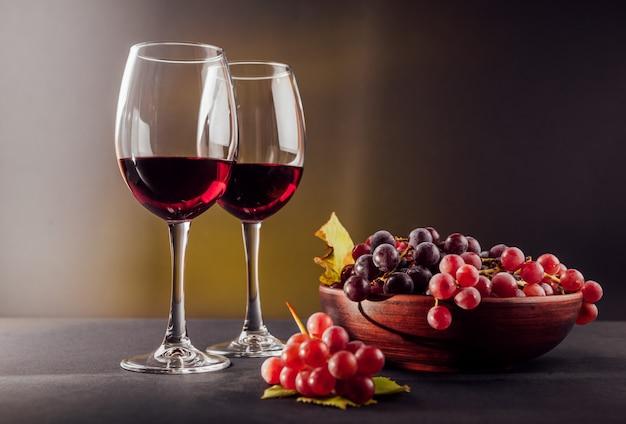 검은 배경에 포도와 와인 두 잔