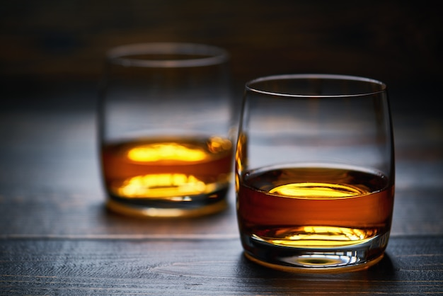 Two glasses of old whiskey on wooden table