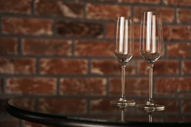 レンガの壁のぼやけた背景に2つのグラス。ロマンチックな夜、デート。碑文の場所。