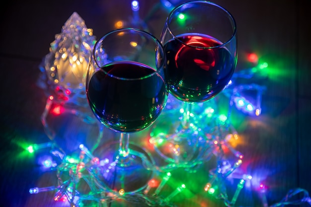 輝くクリスマスツリーの背景に2つのグラスと暗い夜の背景にマルチカラーの花輪。新年のお祝い...