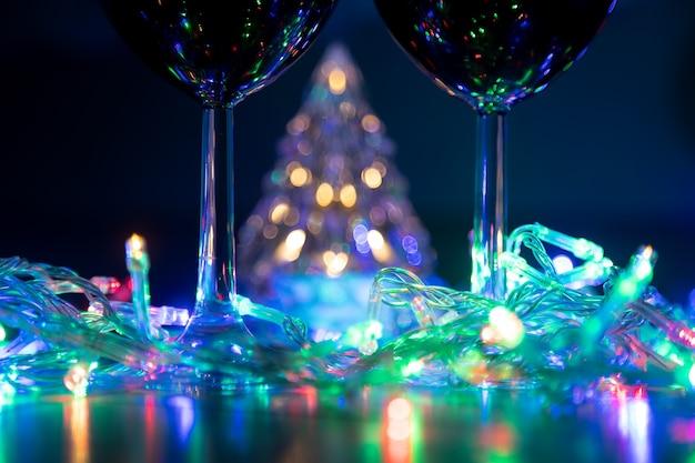 Два бокала на фоне сияющей елки и разноцветная гирлянда в темную ночь