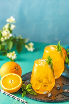 Two glasses of orange ice drink with fresh mint