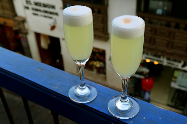 Two glasses of peruvian pisco sour with historic building of cusco old city in peru