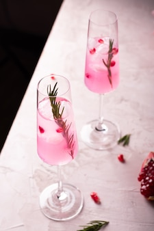 Two glasses of pink pomegranate lemonade on a white table