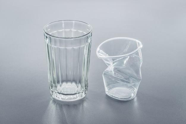 Два стакана, пластик мятый и стекло. крупный план, студийный снимок.