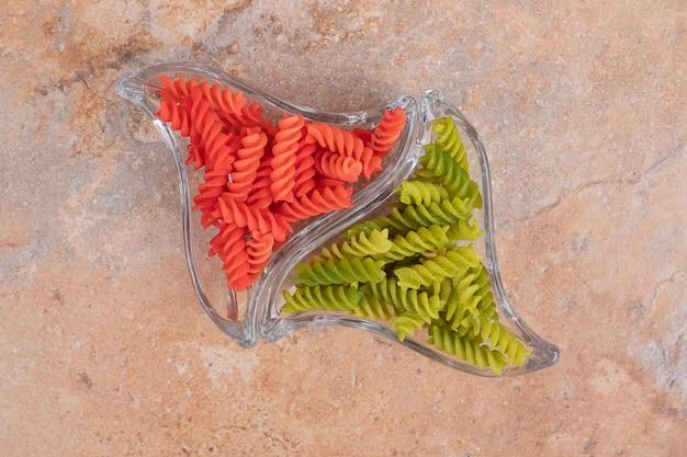 Due bicchieri piatti pieni di pasta a spirale colorata su sfondo marmo. foto di alta qualità