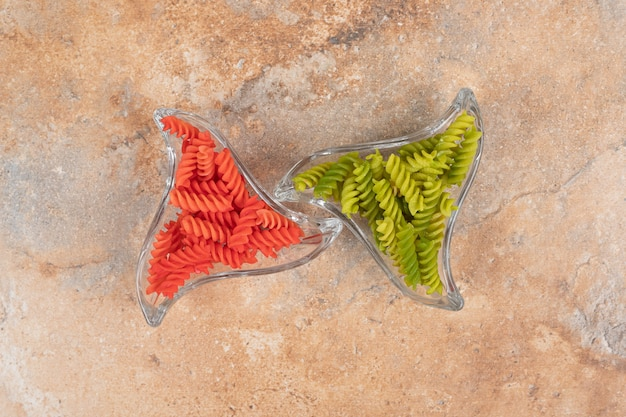 Две стеклянные тарелки, полные красочных спиральных макарон на мраморном фоне. фото высокого качества