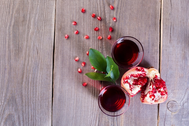 Two glasses of pomegranate juice and ripe pomegranate on a wooden background. healthy drink concept