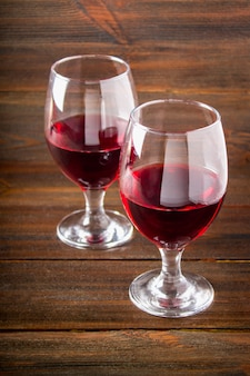 Two glasses of red wine on a brown wooden table. alcoholic beverages.